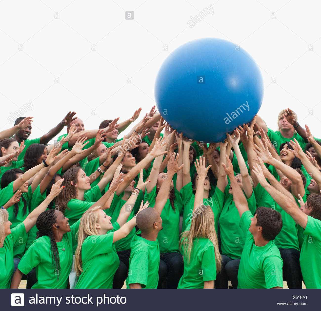 Group of spectators passing giant ball - Stock Image