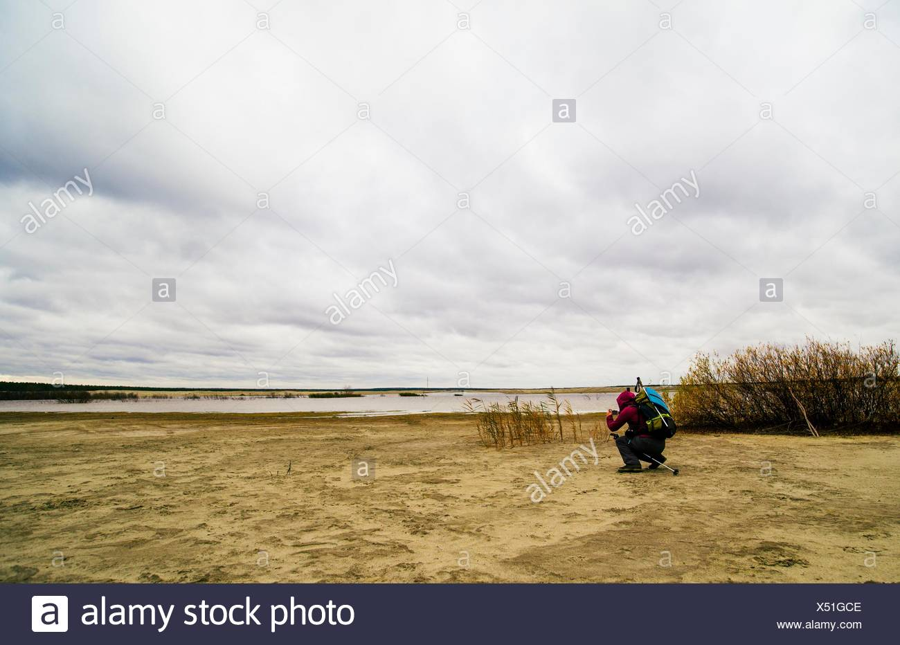 Young man hiking, crouching, taking photograph of lake view, rear view Stock Photo