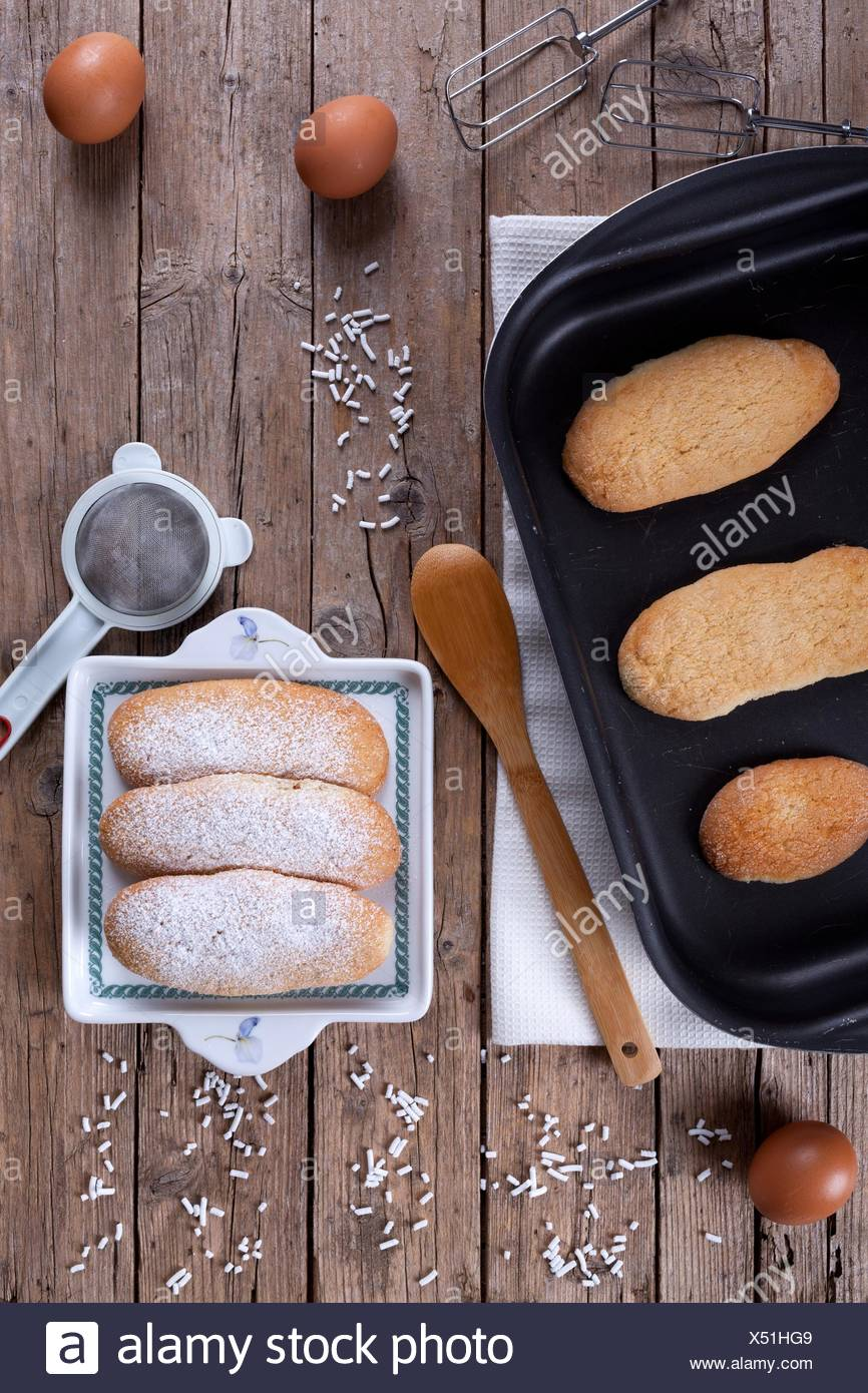 Overhead shot of baking pan with fresh baked ladyfingers (italian savoiardi biscuits) on table with kitchen utensils and eggs. - Stock Image