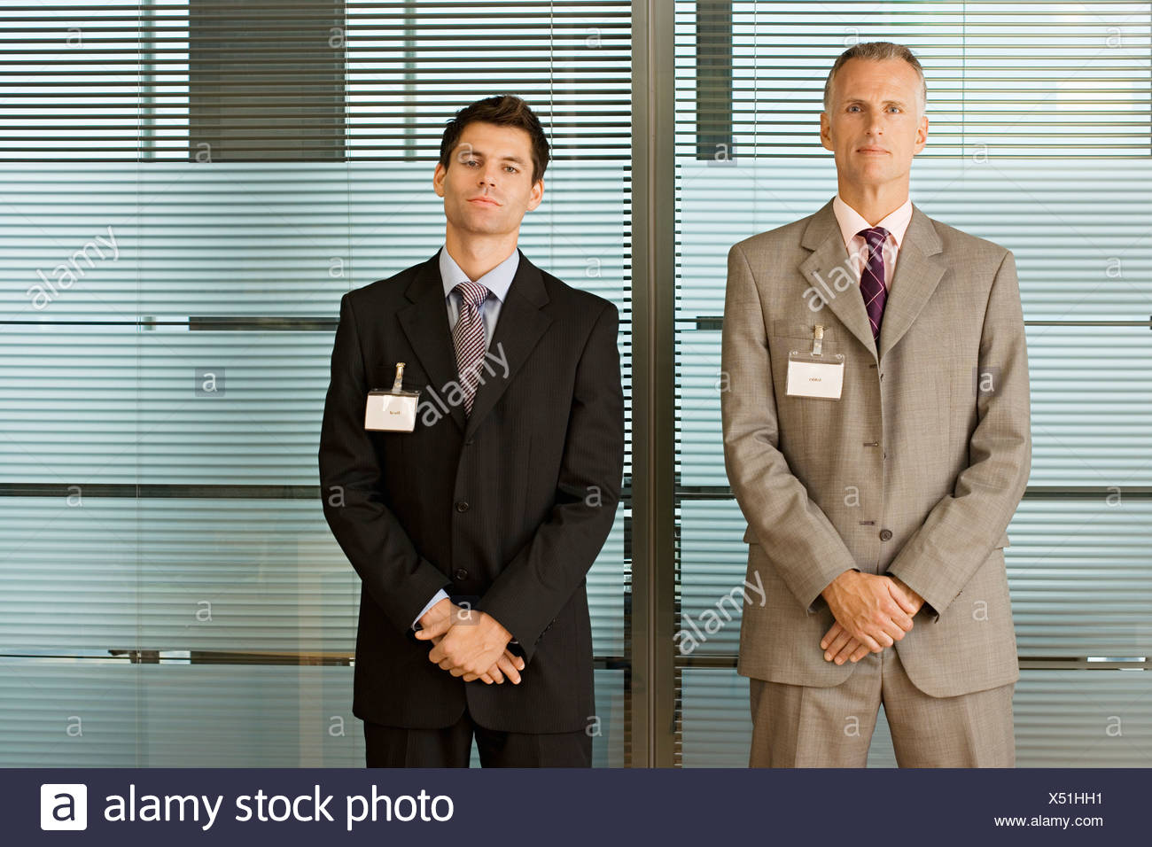 Two confident businessmen wearing identity cards standing side by side front view portrait - Stock Image