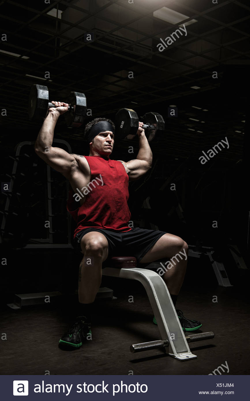 Muscular young man performing shoulder raises with dumbbells in gym - Stock Image