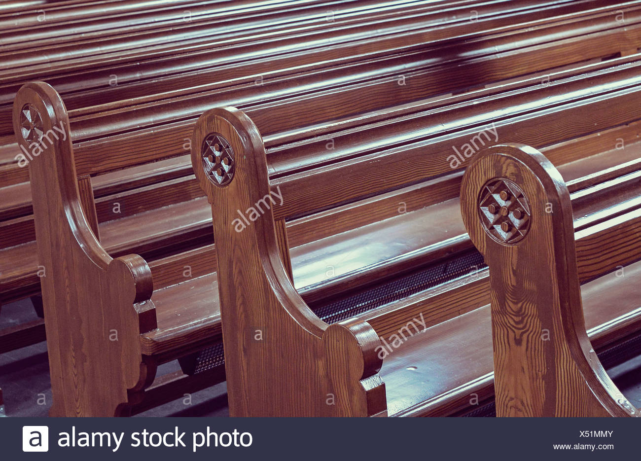 Wooden benches arranged in a row at pew - Stock Image