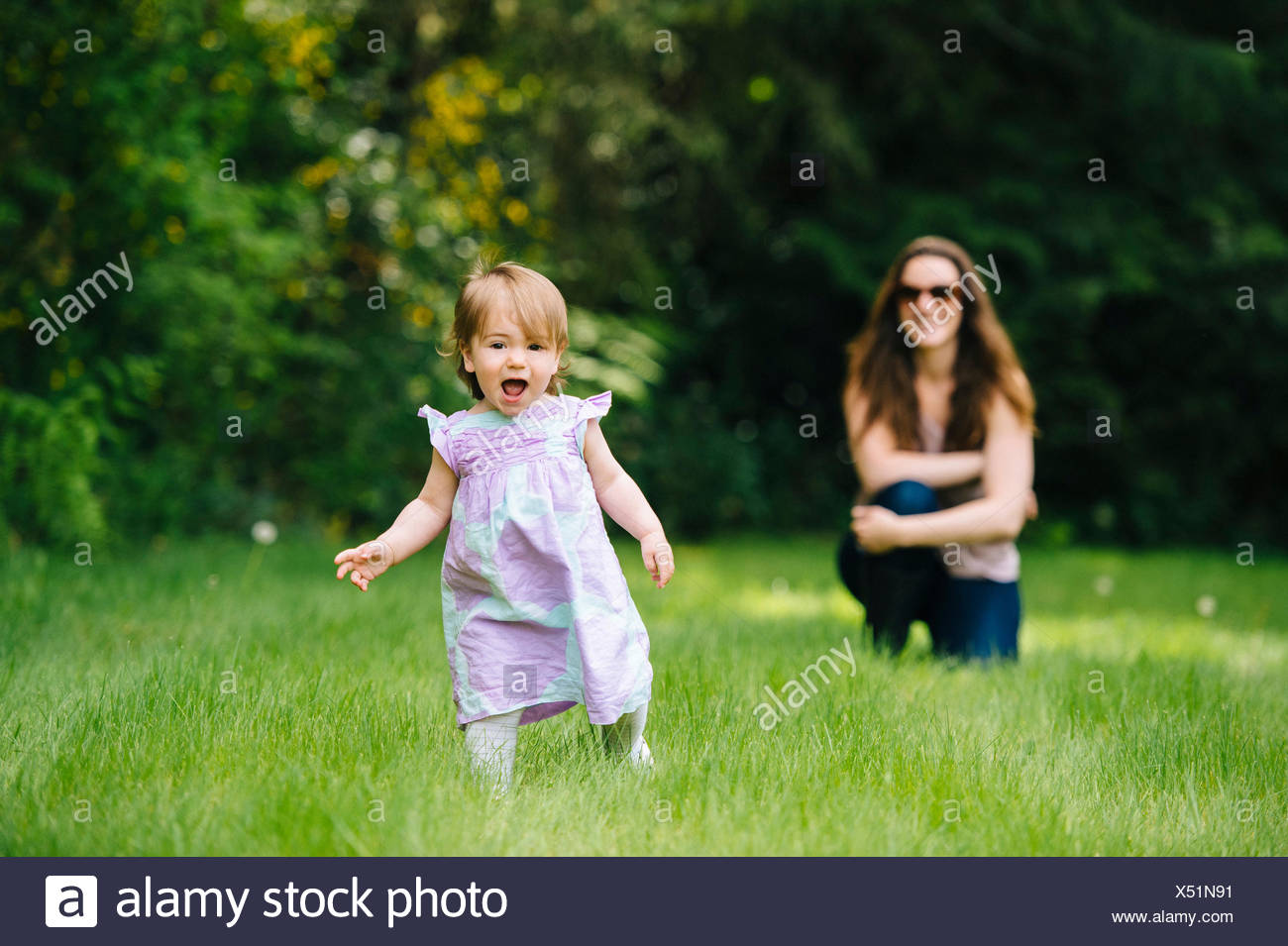 Female toddler running away from watching mother in park Stock Photo