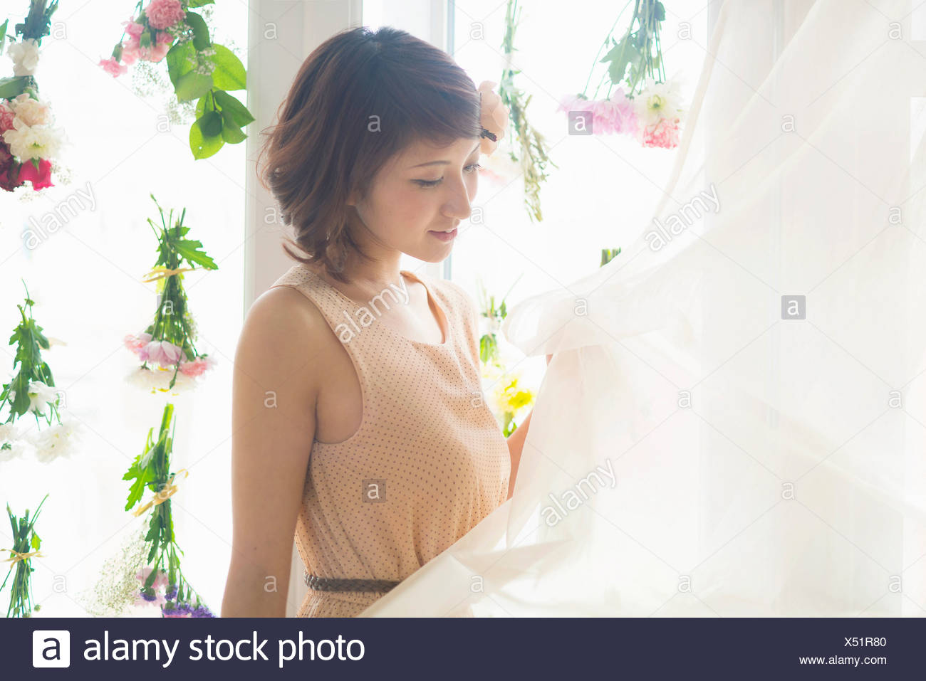 Woman lifting curtains of glass windows with dangling flowers - Stock Image