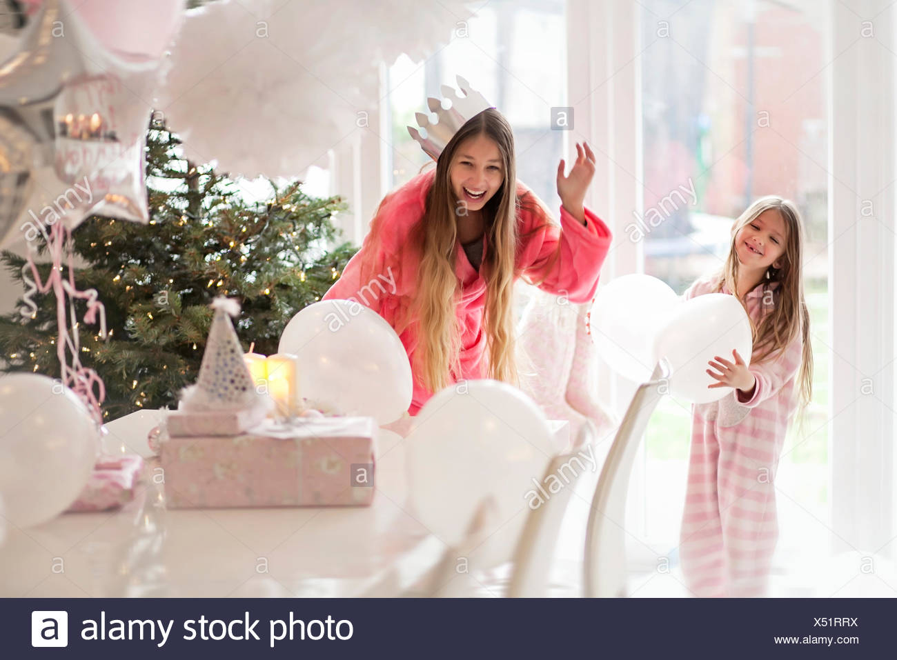 Two girls (4-5,14-15) playing with balloons by Christmas tree - Stock Image