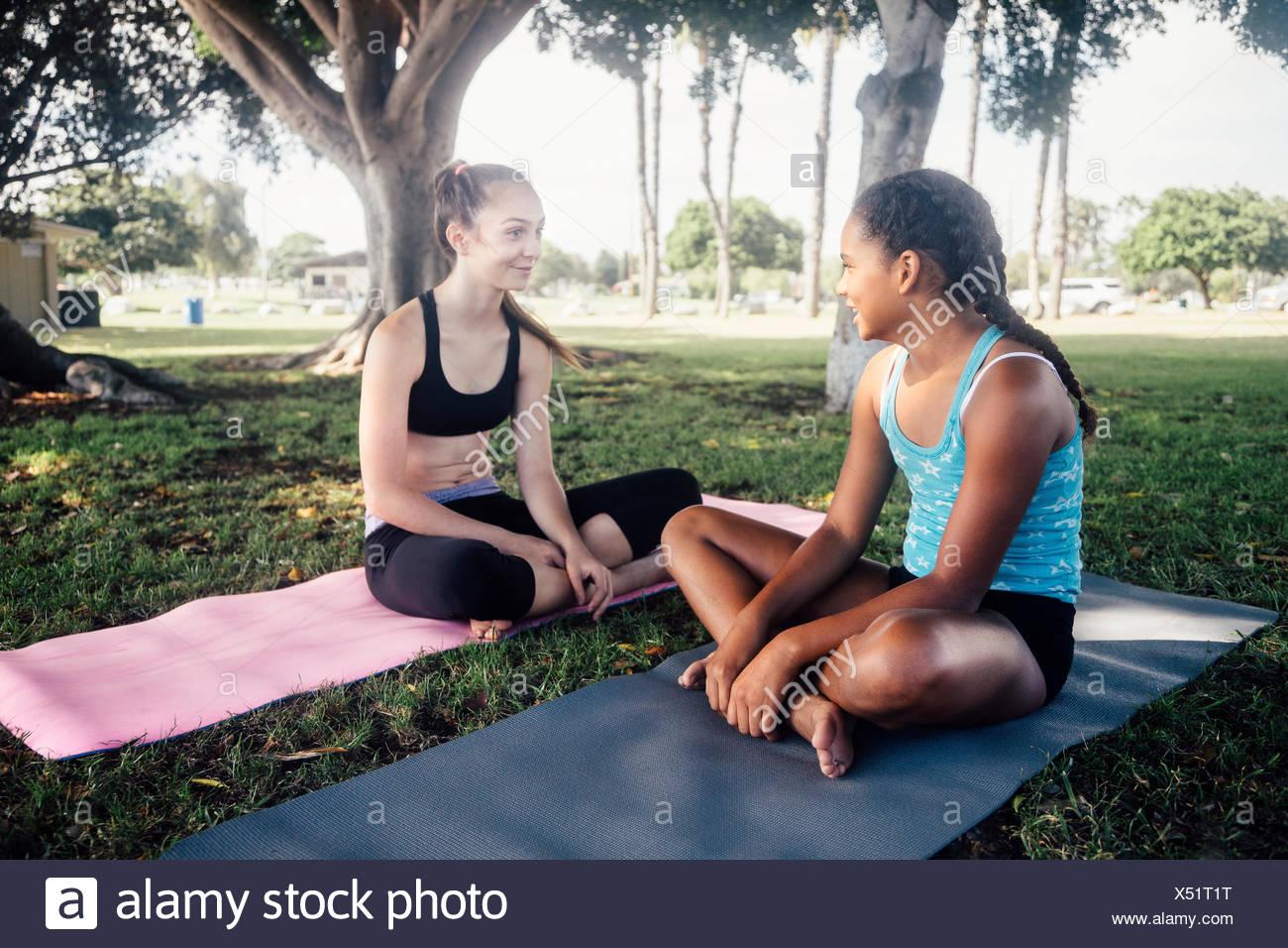 Two schoolgirls chatting on yoga mats on school sports field - Stock Image