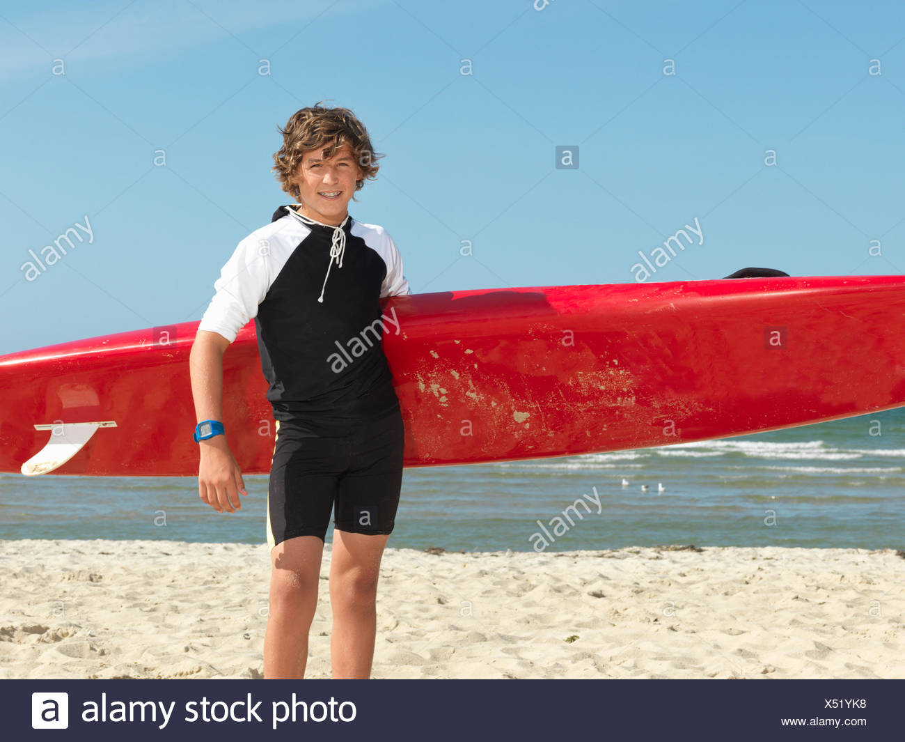Portrait of teenage boy nipper (child surf life savers) with surfboard, Altona, Melbourne, Australia - Stock Image
