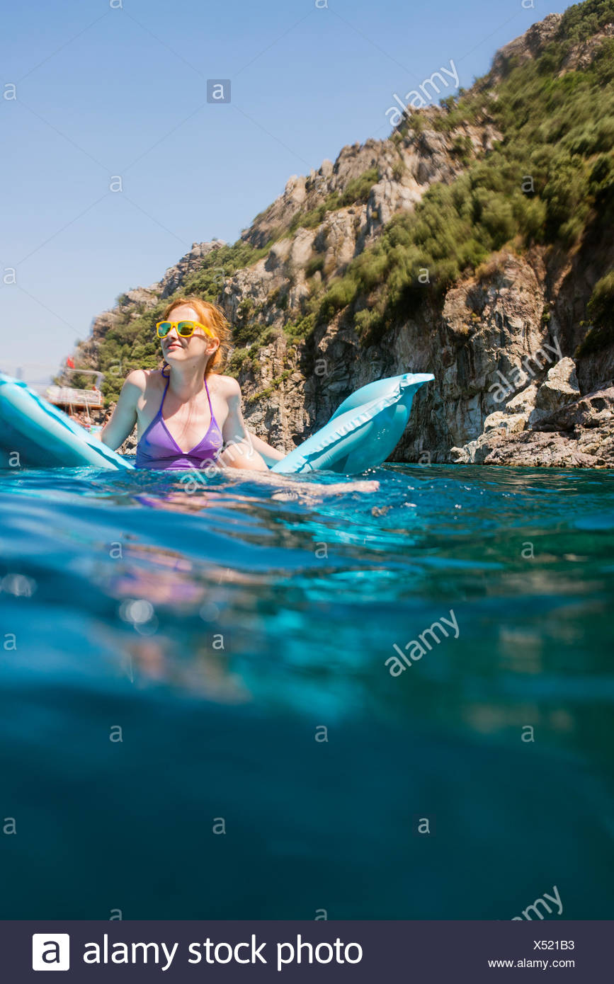 Turkey, Mugla, Marmaris, Woman on blue mattress floating on lake - Stock Image