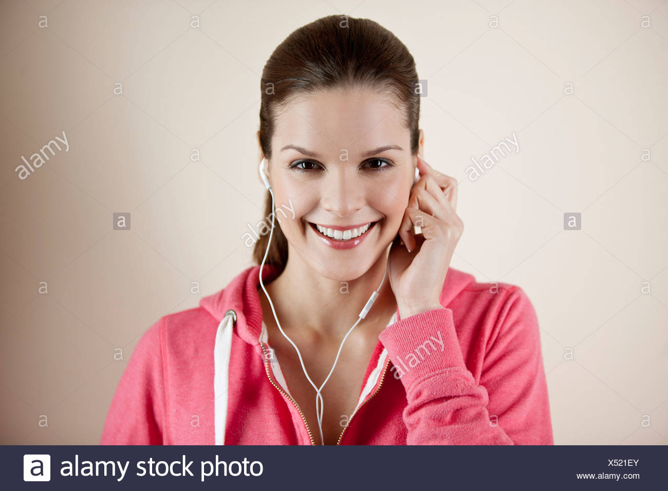 A young woman wearing fitness clothing and earphones, listening to music Stock Photo