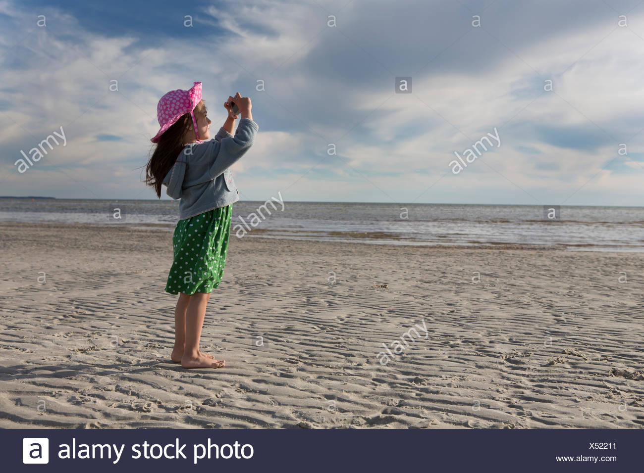 A young girl takes photographs at Skaket Beach. - Stock Image