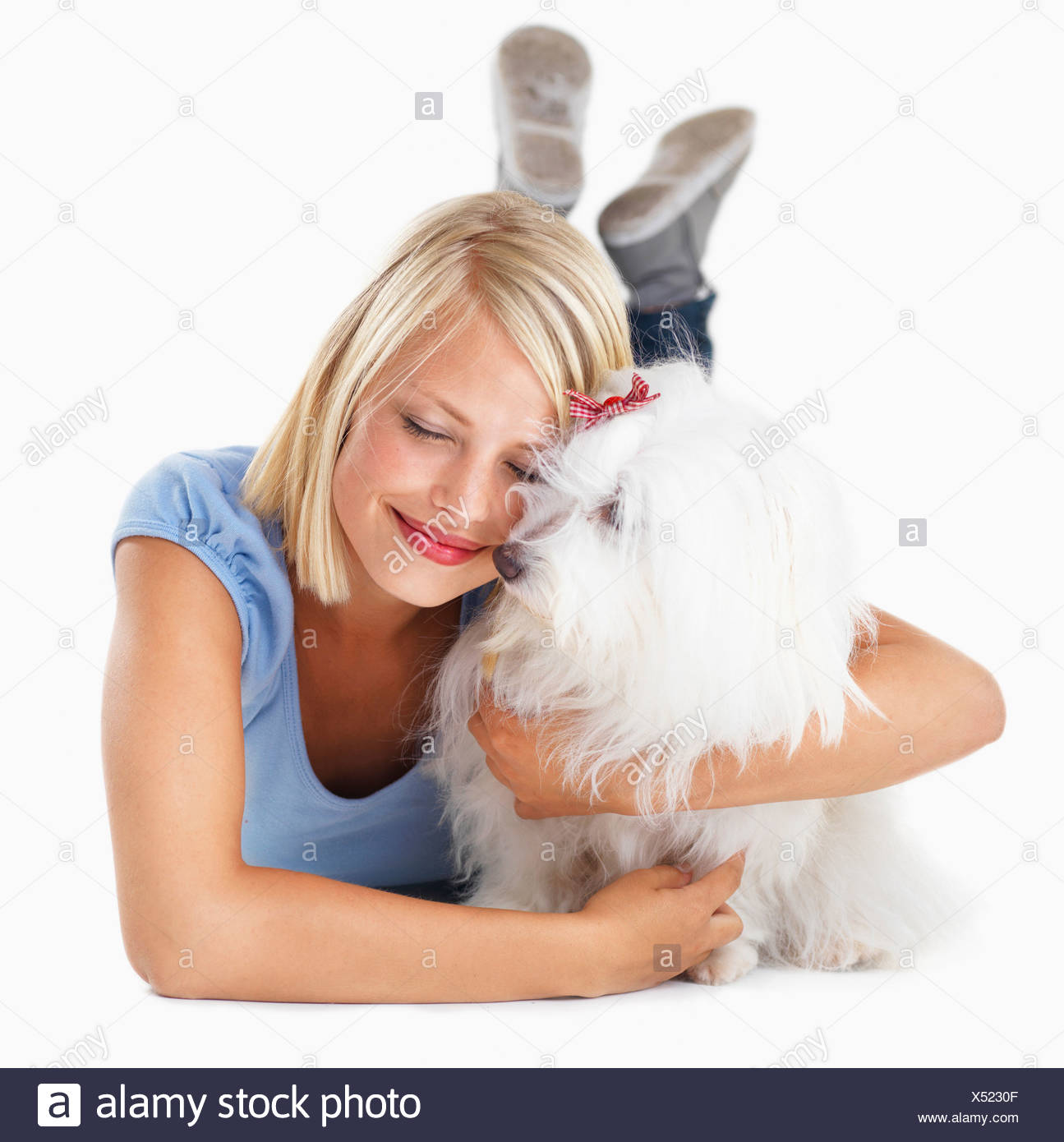 Studio Shot, Portrait of young woman hugging her dog - Stock Image