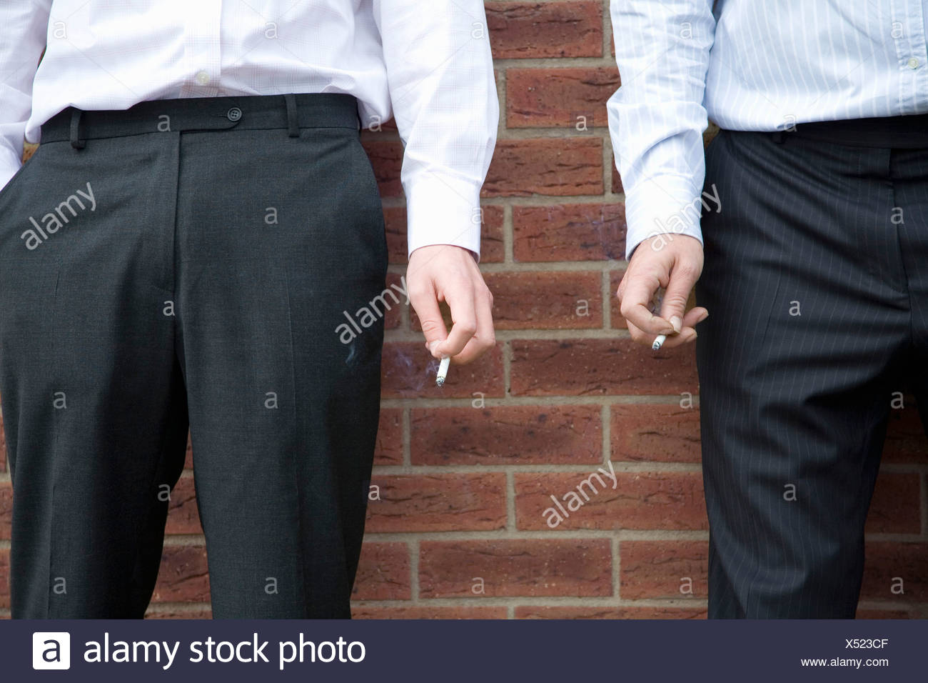 Midsection of two businessmen smoking - Stock Image