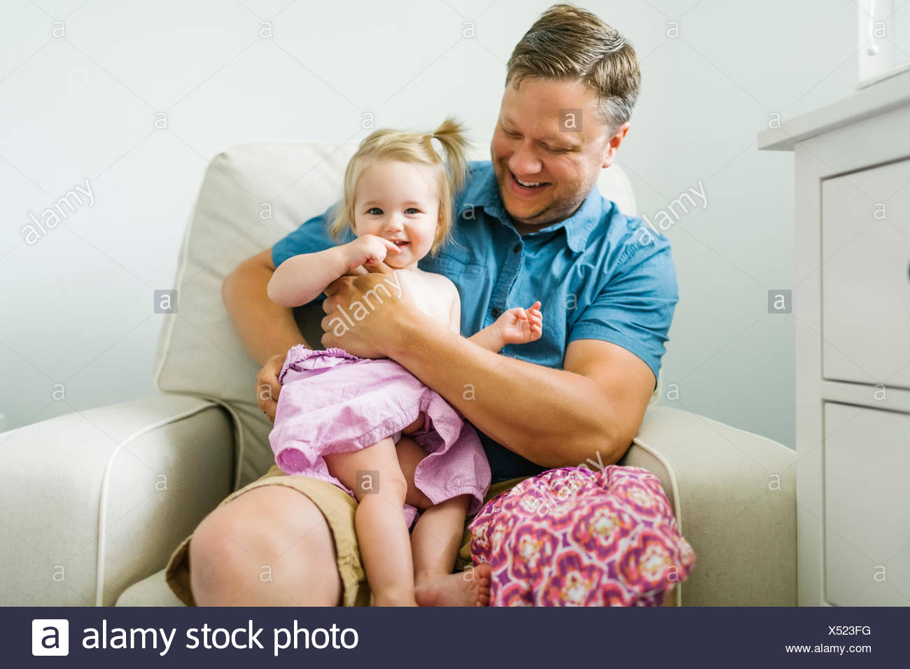 Father with baby girl (12-17 months) sitting in living room Stock Photo