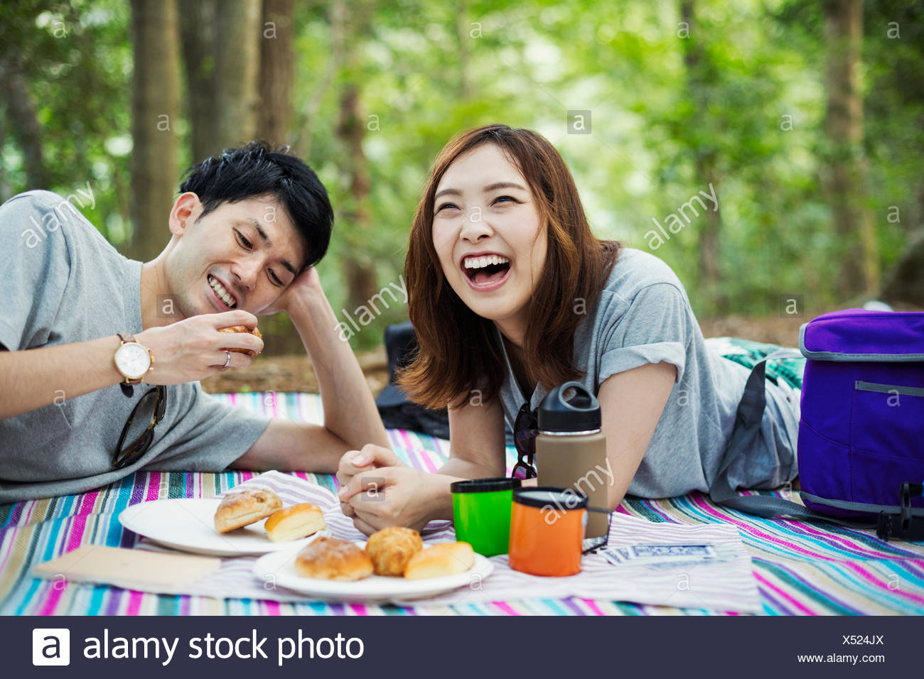 Young woman and man having a picnic in a forest. - Stock Image