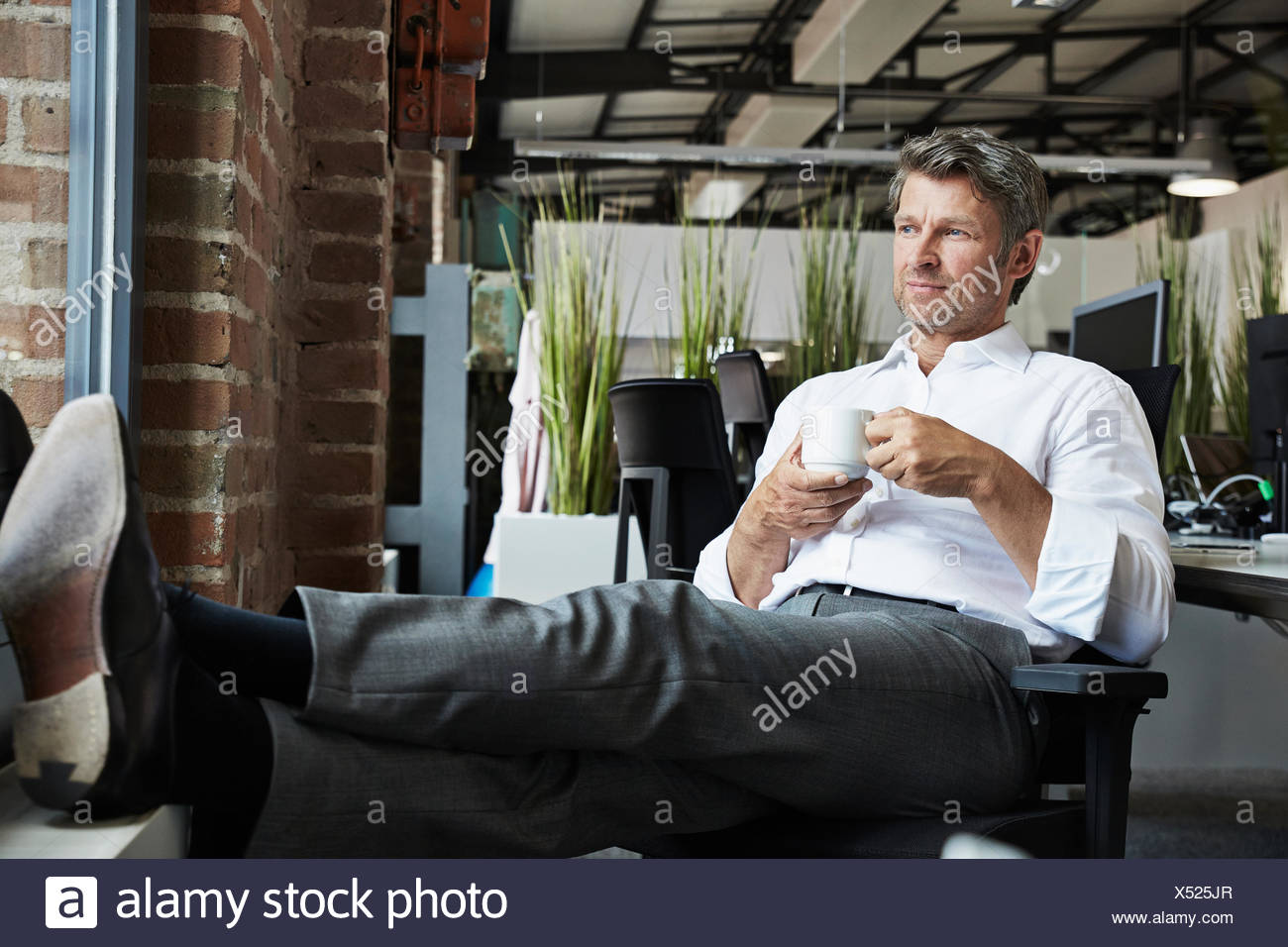 Businessman in office having a coffee beak - Stock Image