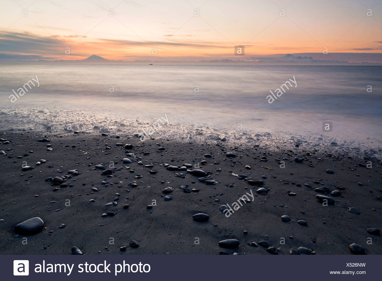 View towards volcanic mountains from the beach at Whiskey Gulch, left, Mount Iliamna, and right, Mount Redoubt, Cook Inlet - Stock Image