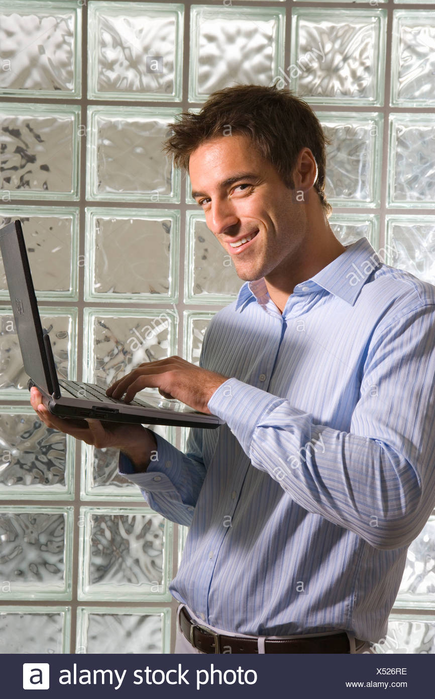 Young businessman using laptop by glass block wall, smiling, portrait - Stock Image