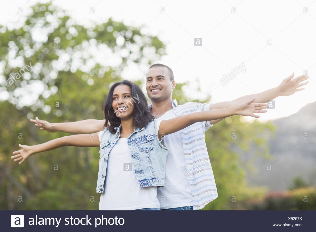 Happy young couple opening arms - Stock Image
