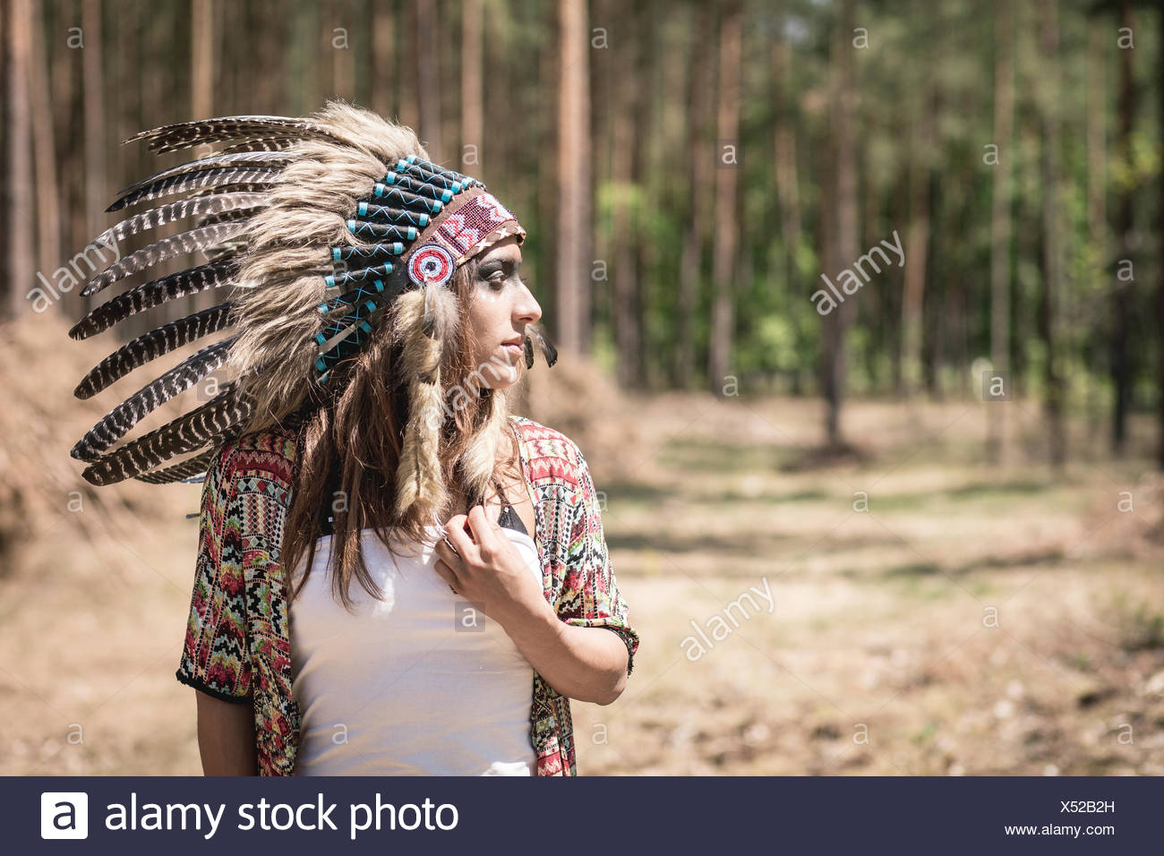 Young woman masquerade as an Indian in the woods - Stock Image