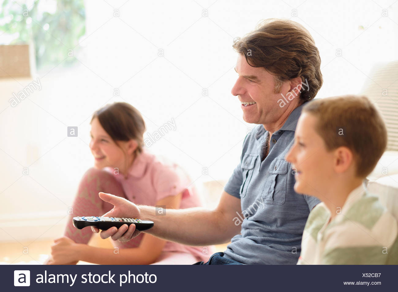 Children (8-9, 10-11) watching TV with their father Stock Photo