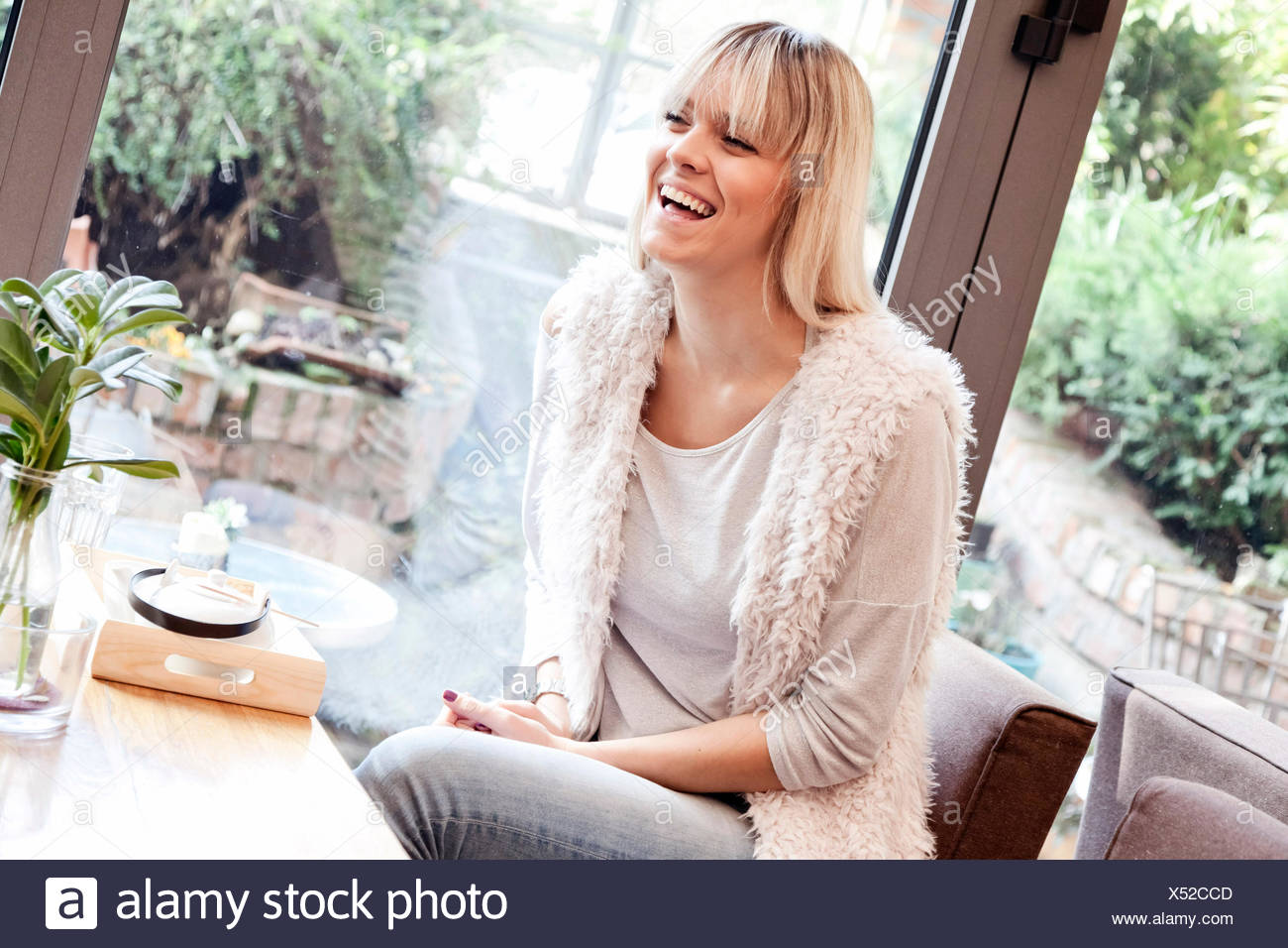 Portrait of young woman in domestic room - Stock Image