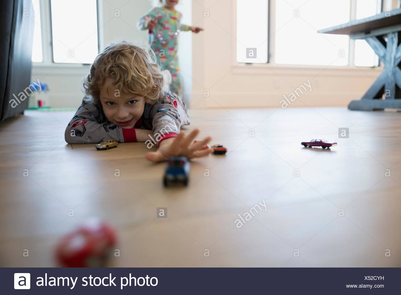 Boy playing with toy cars on floor - Stock Image