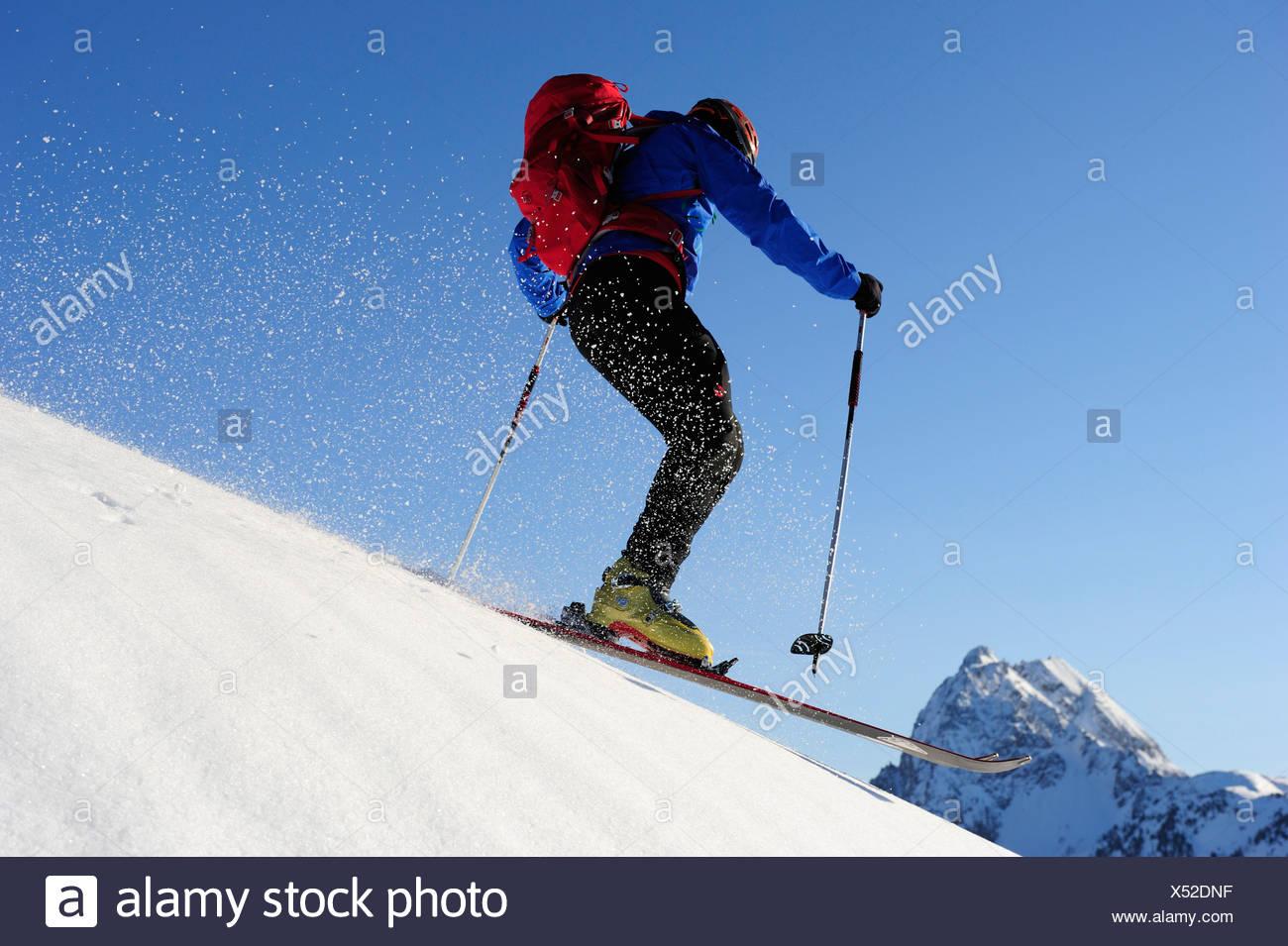 Backcountry skier downhill skiing from Brechhorn, Grosser Rettenstein in background, Kitzbuehel Alps, Tyrol, Austria - Stock Image