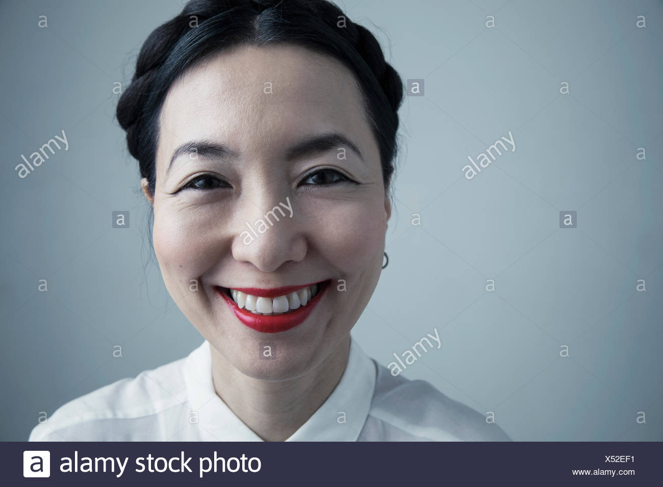 close up portrait happy asian mature woman with braided black hair