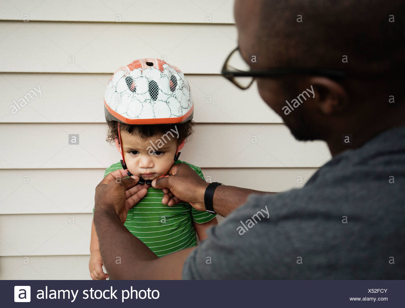 Father putting on helmet for son - Stock Image
