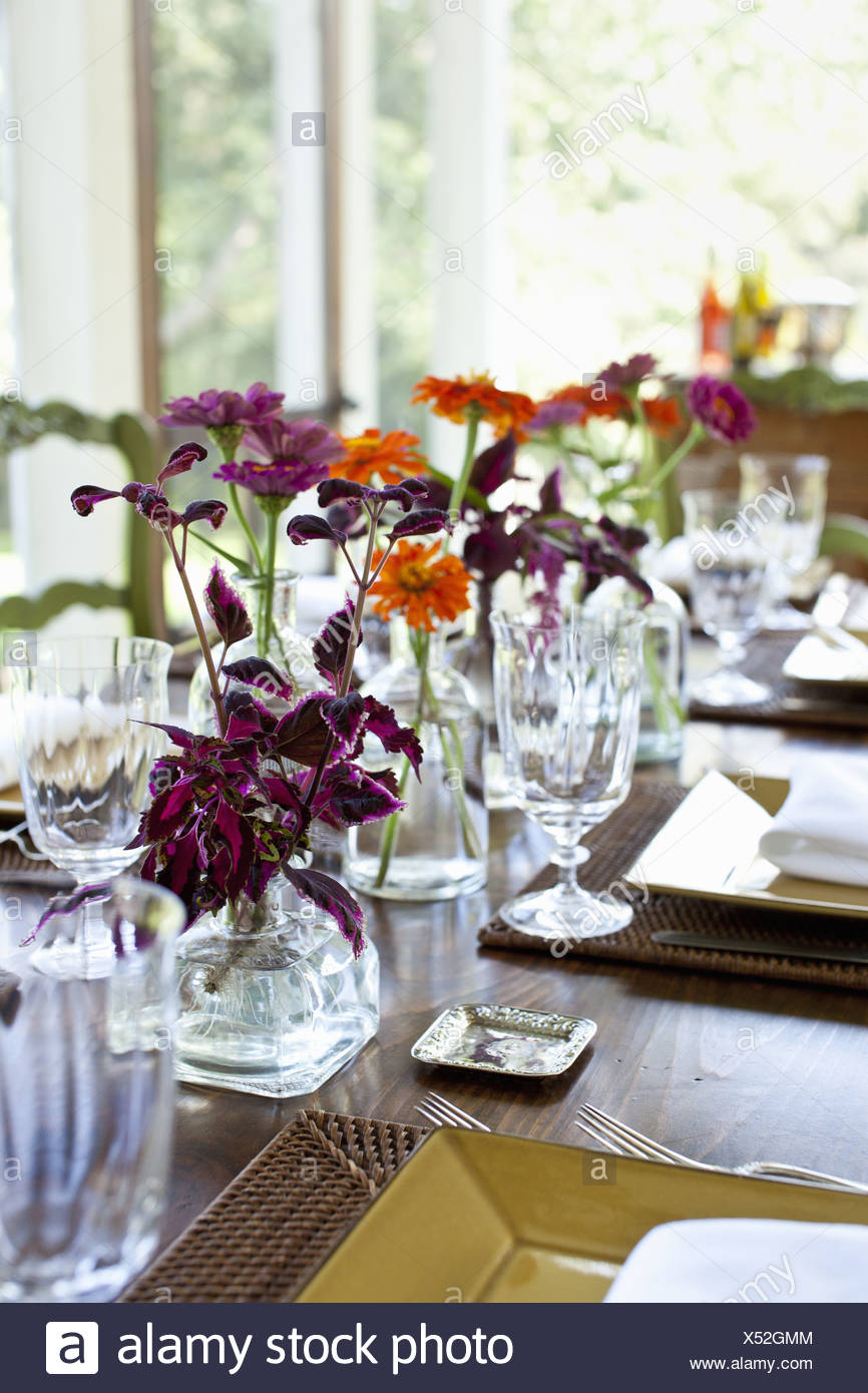Maryland USA table vases of vivid coloured orange and maroon flower as centrepiece - Stock Image