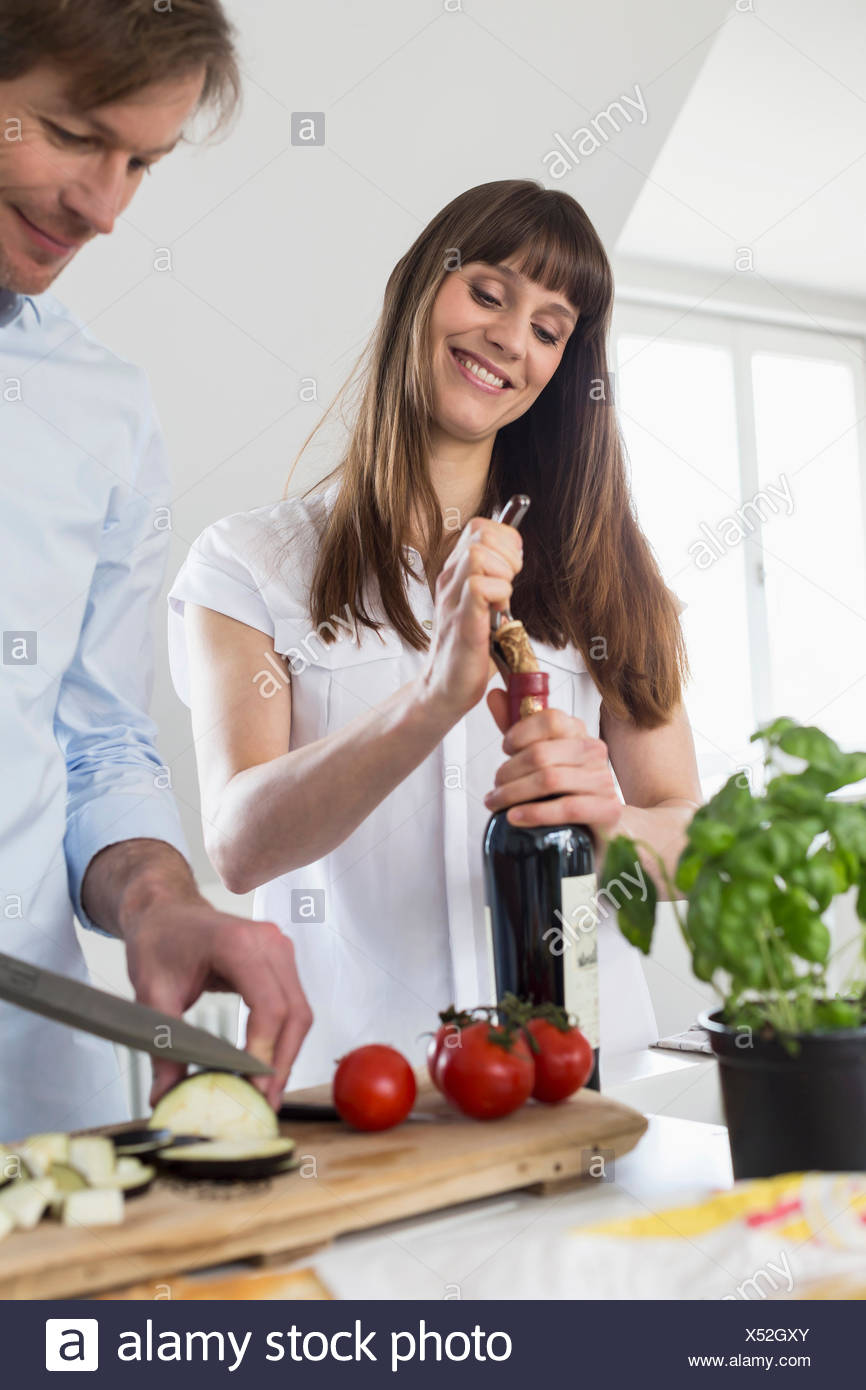 Mid adult woman opening wine bottle while mature man cutting vegetable, smiling - Stock Image