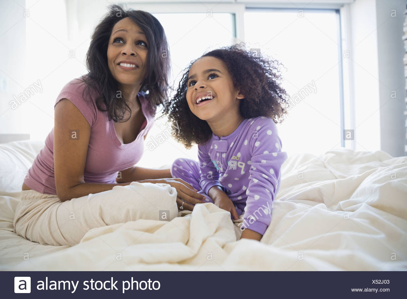 Smiling mother and daughter sitting on bed - Stock Image