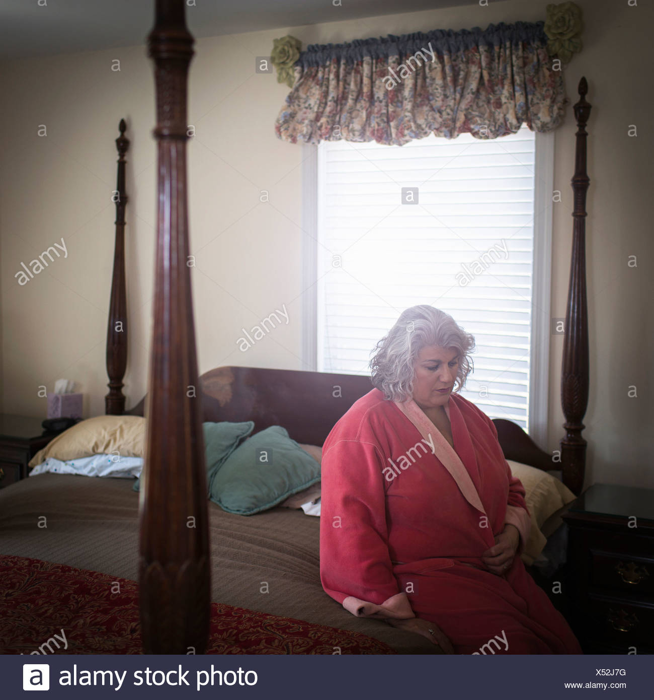 Unhappy mature woman sitting on bed - Stock Image