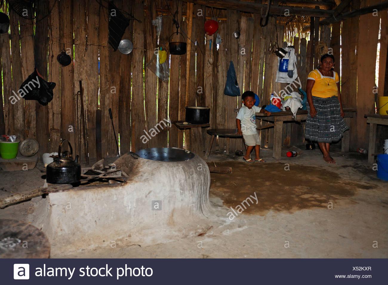 One-room flat, Mayan woman, small boy, fireplace, kitchen utensils, water boiler, Punta Gorda, Belize, Central America - Stock Image