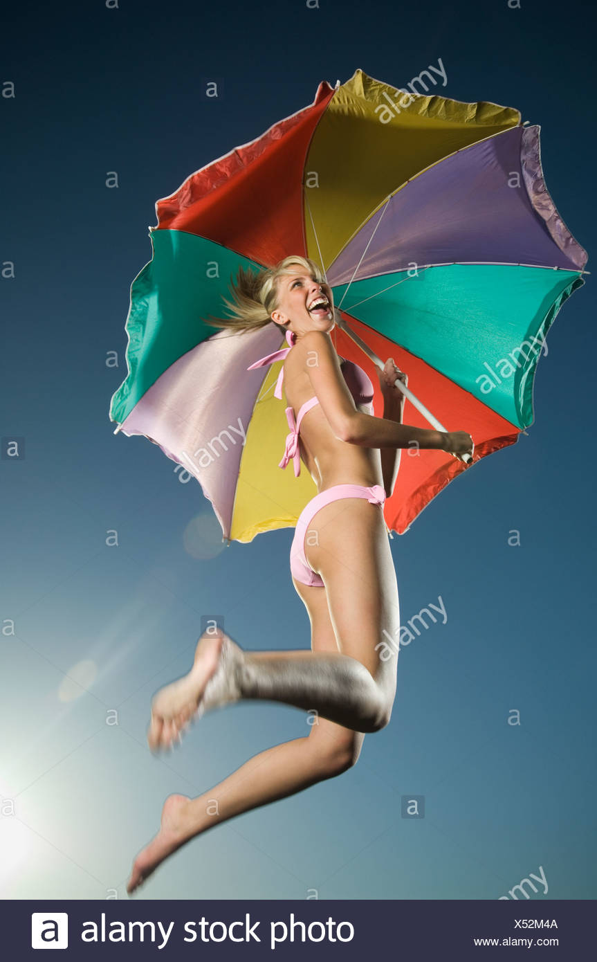 Woman jumping with beach umbrella - Stock Image