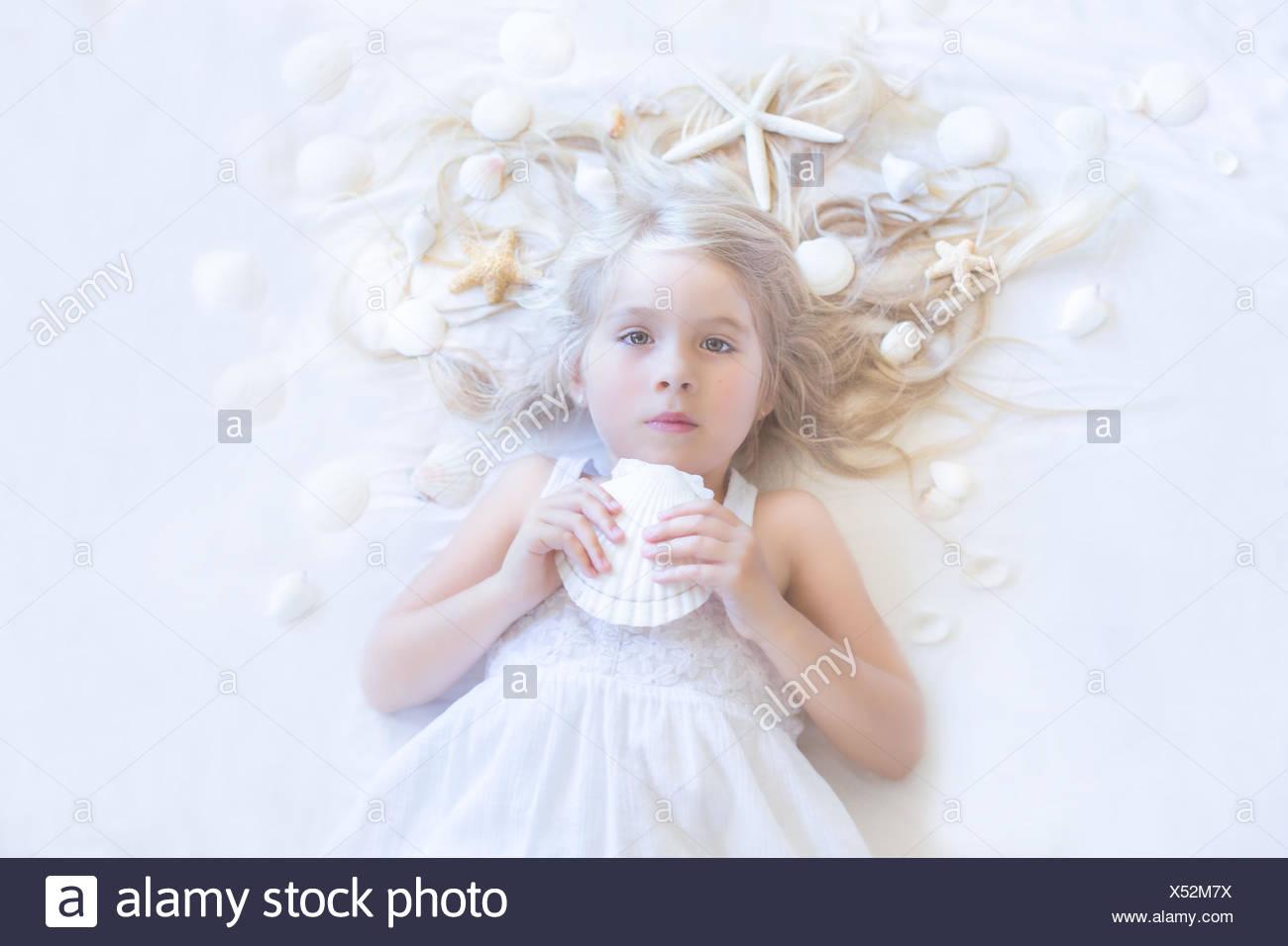 Girl lying on floor with seashells - Stock Image