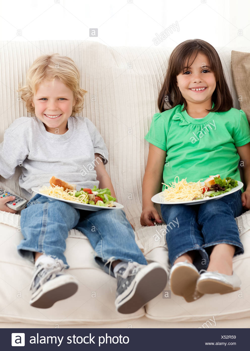 Happy brother and sister watching television while eating pasta - Stock Image