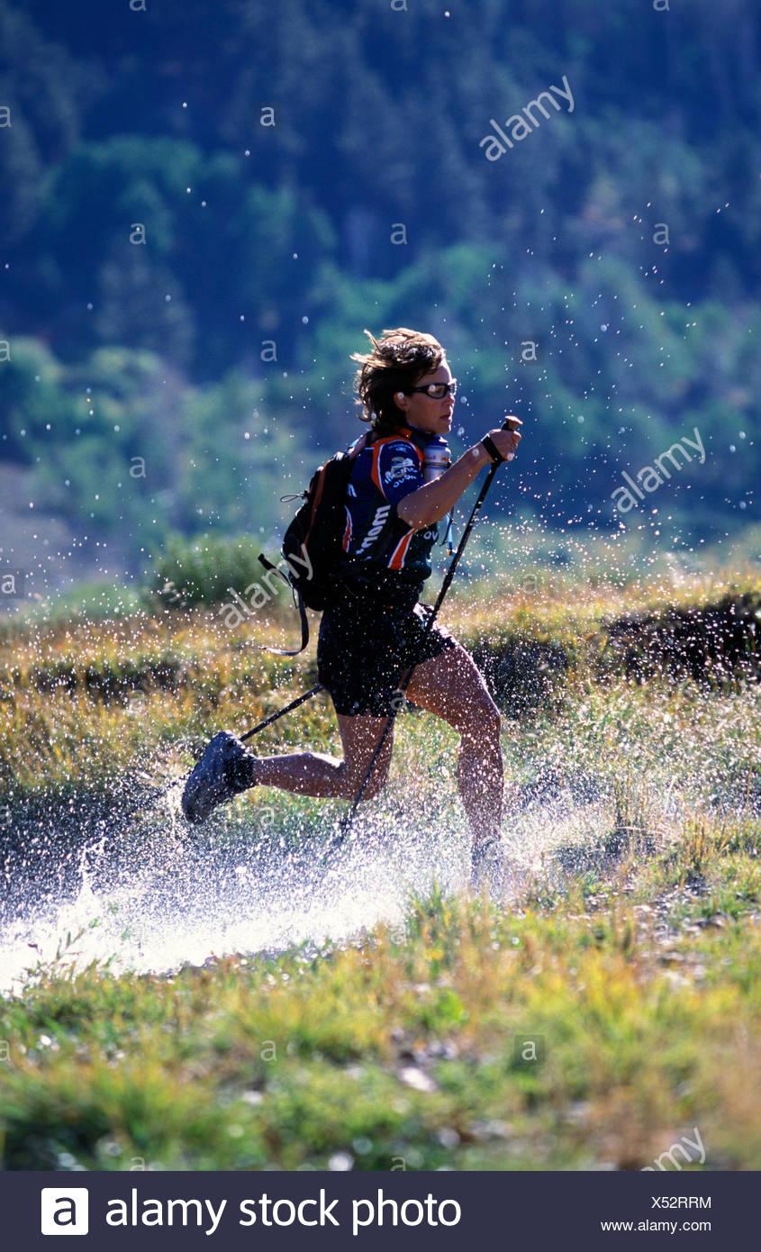 One female adventure racer runs through river crossing. Lake Tahoe California. - Stock Image