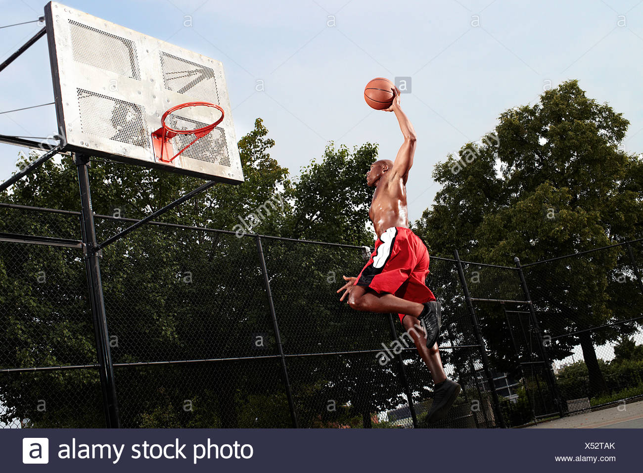 Young man leaping at basketball hoop - Stock Image