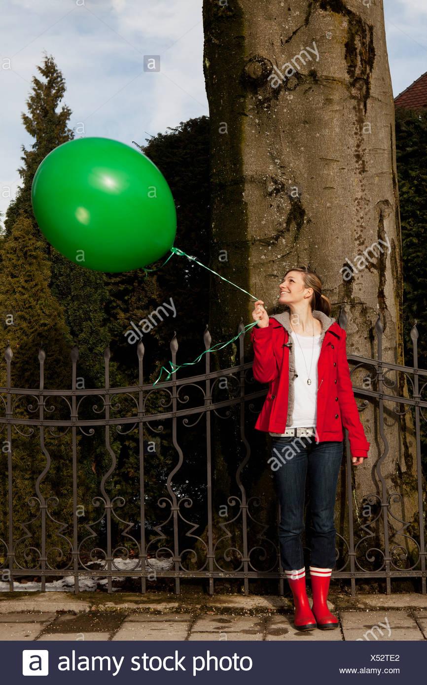 Woman holding green baloon - Stock Image