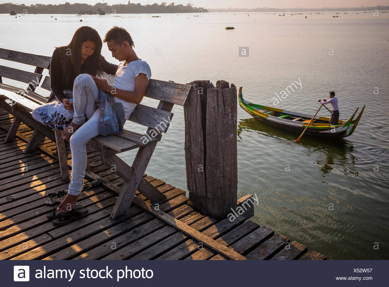 A young couple sit on a pier bench as a fishing boat passes behind them. - Stock Image