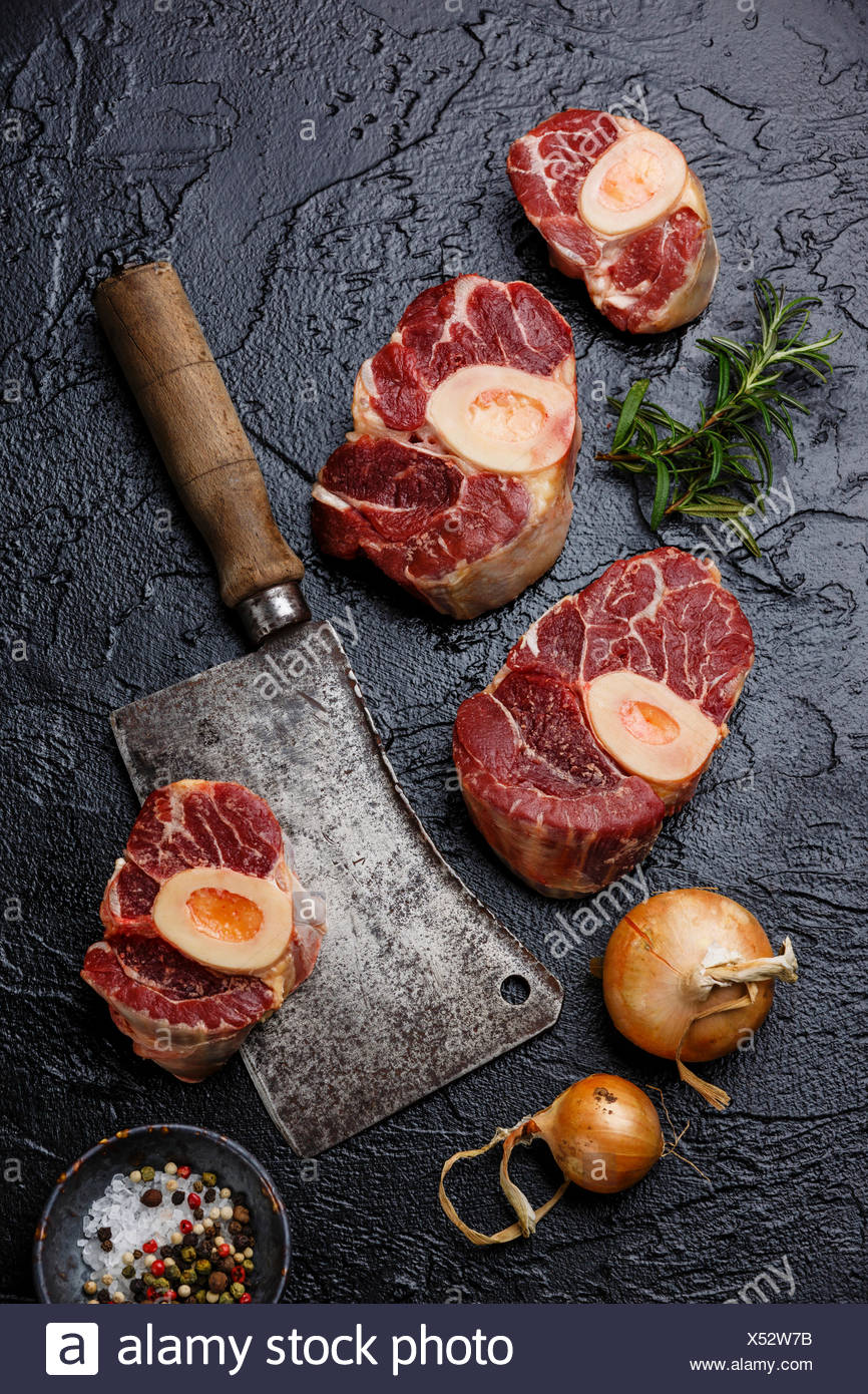 Raw fresh cross cut veal shank and ingredient for making Osso Buco on black background with meat cleaver - Stock Image