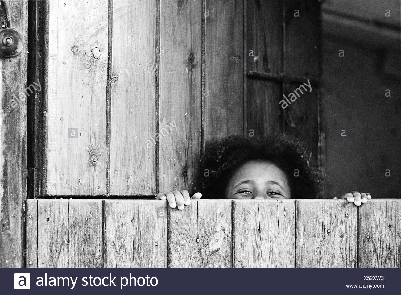 Girl peeking over the edge of a stable door - Stock Image