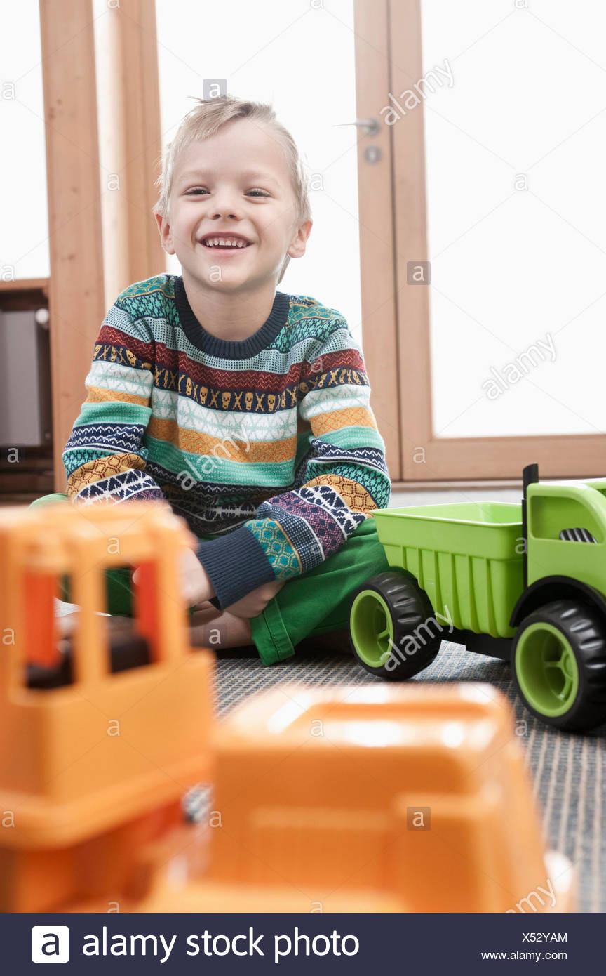 Portrait of smiling little boy sitting on ground of his kindergarten - Stock Image