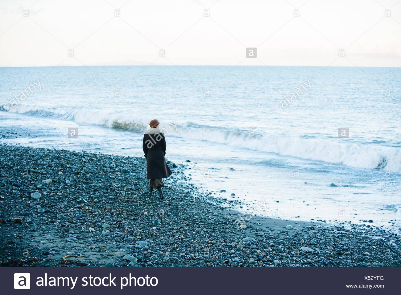 Rear view of woman strolling on beach - Stock Image