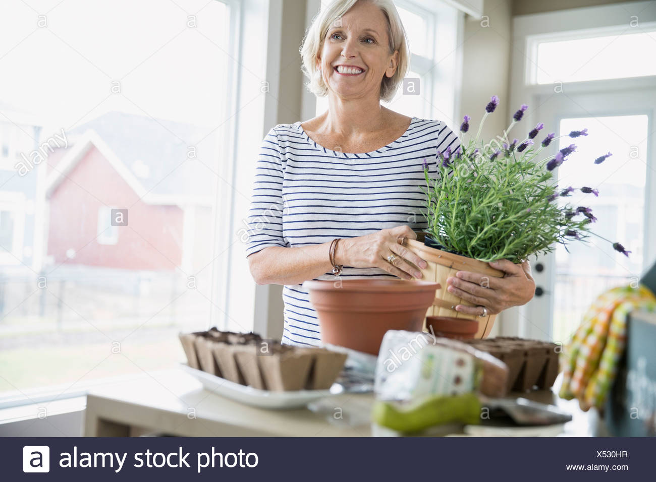 Smiling woman with garden supplies - Stock Image