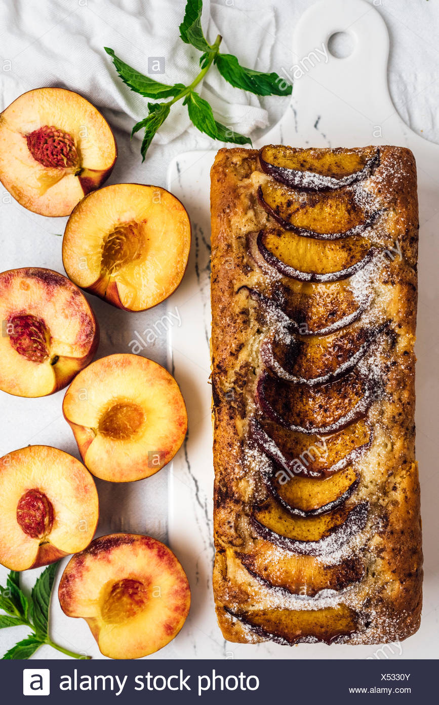 A whole peach bread topped with cinnamon and brown sugar on white marble board photographed from top view. Accompanied by halved peaches. - Stock Image
