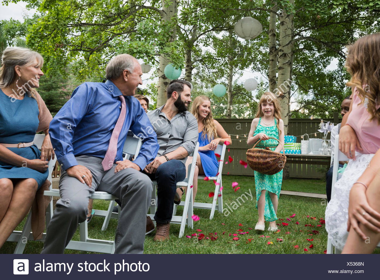 Wedding guests watching flower girl spread petals backyard - Stock Image