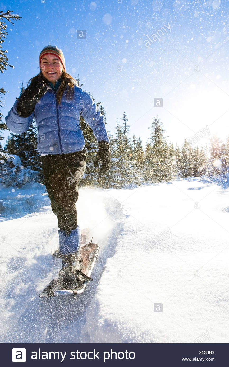 Young woman on snowshoes enjoy the outdoors near Homer, Alaska during winter. - Stock Image