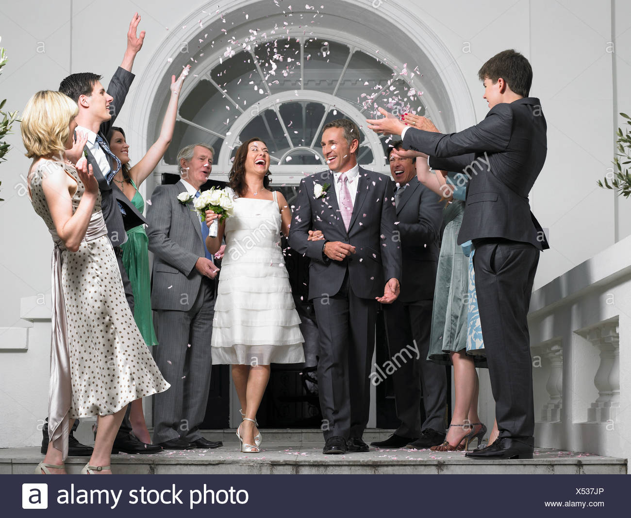 Guests throwing confetti over bride and groom - Stock Image